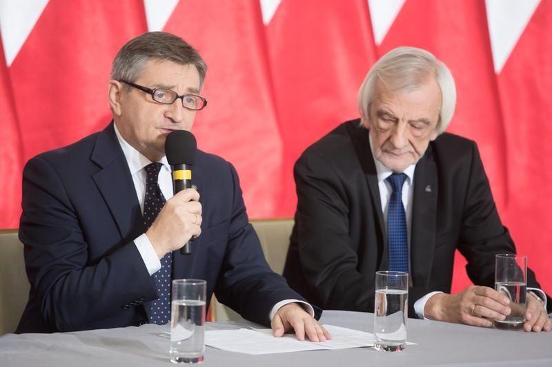 siedza za stołem, Kuchciński z mikrofonem