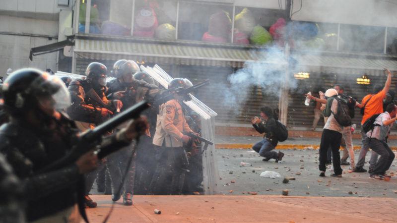 Wenezuelska policja używająca gazu łzawiącego wobec studentów protestujących na ulicach Caracas, źródło Wikipedia